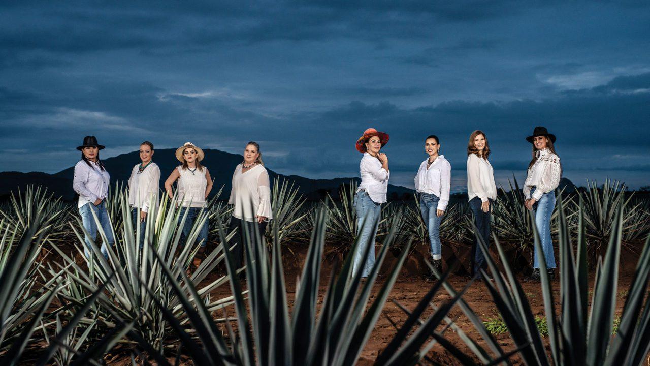 """テキーラ業界で活躍する女性たち 長年男社会であったテキーラ業界。Forbes Méxicoが最近組んだ特集の中で、テキーラ製造で女性の視点が勝ち得た成功と待ち受ける課題について熱く語る女性たちの素顔が明らかになる。 テキーラへの世界的評価を優れた感性と新しい発想によって不動のものとする、これらの女性たちは、テキーラ界におけるたおやかにして大胆な「革命」の旗手ではないであろうか。 """"LAS MUJERES DEL TEQUILA"""", ESPECIAL, FORBES.COM.MX Septiembre 2021 Texto por Viridiana Mendoza Escamilla y Raúl Curiel Fotos por Fernando Luna Arce メキシコの代表的な産業の一つであるテキーラ 約170社の蒸留所が創業するこの業界の特徴を数字で見てみよう。農作業(アガベ栽培)を中心に約7万人の雇用を創出し、3億7,400万ℓ(2020年度)の総生産量の内、2億8,600万ℓが世界120カ国以上に輸出され、23億ドルの外貨を獲得している。このように、テキーラが、メキシコの経済産業に於いて極めて堅固な存在であることは明白であるが、他方イメージで捉えてみると、口髭を蓄えた馬に乗ったカウボーイという地方の男性的なイメージが長い間持たれていたことも事実である。しかし、数年前から、こうしたステレオタイプにも変化をもたらす新風が吹き始めており、その担い手として、業界への女性の参加が着実に拡大して来ている。 荒波の中に勇敢にも飛び込んで行った女性たちは以下の通りである。括弧内は主宰する組織または経営する蒸留所である。なお、スペイン語の人名につきものの煩雑さを避けるために、以下の本文中は下線を施した名前のみをカタカナ表記とする。 Gabriela Cañedo(Universo Tequila) Rubí Esmeralda Partida(Tequila Tres Mujeres) Mayra Paola Martínez Reyes(Tequilera de Arandas) Marcela Orendain Giovannini(Tequila Orendain) Leticia Hermosillo Ravelero(Tequila Puerto de Hierro) Iliana Elizabeth Partida(Hacienda de Oro) Carmen Villarreal Treviño(Casa San Matías) Guadalupe Newton Frausto(Destilería Santa Lucía) Bertha González Nieves (Casa Dragones) Guadalupe Lucía (Melly) Barajas Cárdenas (Vinos y Licores Azteca) こうした変化は、新たな現象として市場での女性消費者が増加している中にも確認される。業界内での変化は、陣頭指揮を取る女性経営者の登場と、大手メーカーでも女性の管理職への登用が増加していることに明確に示されている。このように明言するのはCNITによるテキーラ専門家(Conocedora del Tequila)の認定を受けた、""""Universo Tequila""""を主宰するガブリエラである。 家族経営と現実的な後継者の問題 現在約170社存在するテキーラ蒸留所の中で、少なくとも12社が女性経営者によるものである言われている。この数字の大小はさて置き、伝統的に閉鎖的な男業界への女性の参入をもたらした根本的要因として、客観的な必要性があることが指摘できる。家族経営の蒸留所では、後継者の問題は避けて通れない側面があるからである。家族経営のメーカーの社長には、後継者になる息子がいない場合が少なくない。しかし、娘はいることから、女性を会社の代表として業界に含めることは、言わば背に腹はかえられぬという部分が根底にあるにせよ、業界内で世代的な受容が高まっているという現実がある。そこには、以前の世代の受けた教育と今日の世代のそれとの間には違いがあり、そこから状況への変化が起きつつあるということになる。親の経営する蒸留所で既にマーケテイング・営業職から社長になったイリアナは典型的な一例である。しかしながら、現状は、彼女のような事例が一般化しているとは言い難く、女性による蒸留所経営が、選択肢の「一つ」であると普通に認識されるにはまだ道半ばであると彼女は語る。 イリアナの言葉を借りると、そうした立場にある女性たち自身も、実は新たな心構えが必要であり、それは自分が望むことは叶えることができる、能力の点で男性に劣って"""